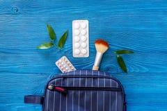 Den kosmetiska påsen med preventivmedel och preventivpillerar på blått bordlägger copyspace för den bästa sikten för bakgrund Fotografering för Bildbyråer