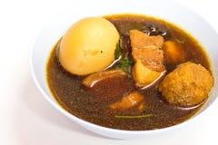 Den kostade-upp thailändska matmenyn är ägget och griskött i söt brun sås royaltyfria bilder