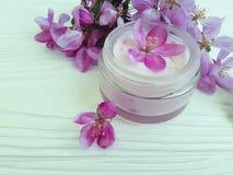 Den kräm- kosmetiska rosa färgen för friskhet för behållareskyddswellnessen blommar på vitt trä royaltyfri fotografi