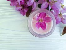 Den kräm- kosmetiska rosa färgen för friskhet för wellnessen för behållareskyddsprodukten blommar på vitt trä arkivfoton