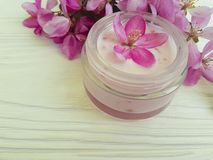 Den kräm- kosmetiska rosa färgen för friskhet för wellnessen för produkten för behållareskyddstoalettartikeln blommar på vitt trä fotografering för bildbyråer