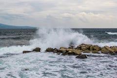 Den kraftiga vågen i havet som kraschar mot, vaggar överföring upp sprejer av vitt skum i himmel med seagullen för cirrusmolnmoln royaltyfria foton