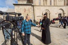 Den kristna prästen ger en televisionintervju nära den Svetitskhoveli domkyrkan som byggs i det 4th århundradet Royaltyfri Fotografi