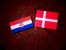 Den kroatiska flaggan med danska sjunker på en isolerad trädstubbe Fotografering för Bildbyråer