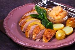 Den kryddade långsamma stekanden, äpplesås, spenat och potatis, tjänade som på rosa färgplattan arkivfoton