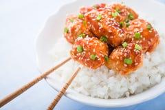 Den kryddiga sötsaken och sur höna med sesam och ris stänger sig upp på blå bakgrund Fotografering för Bildbyråer