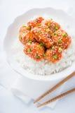 Den kryddiga sötsaken och sur höna med sesam och ris stänger sig upp på vit bakgrund Royaltyfri Foto