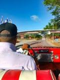 Den kubanska chauff?ren av en cabriolet som k?r bilen fotografering för bildbyråer