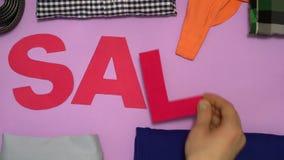 Den kulöra ljusa försäljningsinskriften som snidas från papp, ligger på bakgrunden av kläder Händer snappar ut kläderna som de sä stock video