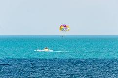 Den kulöra parasailvingen drog vid ett fartyg i havsvattnet, Parasailing också som var bekant som parascending eller parakiting Royaltyfri Foto