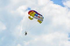 Den kulöra parasailvingen i blåtten fördunklar himmel, Parasailing Royaltyfri Bild