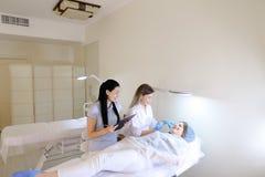Den kvinnliga ögonbryntatueringförlagen undervisar flickastudenten att arbeta med c Royaltyfria Foton