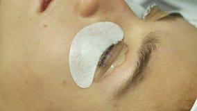 Den kvinnliga ögonnärbilden med en selekonovy samkopiering för en ögonlock, förlagen av salongen sätter slätar vit kräm på ögonfr stock video