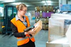 Den kvinnliga arbetaren avläser packen i lager av spedition Arkivfoto