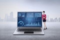 Den kvinnliga arbetaren lutar på bärbara datorn med diagrammet Royaltyfri Bild
