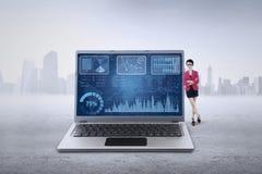 Den kvinnliga arbetaren lutar på bärbara datorn med diagrammet Fotografering för Bildbyråer