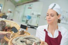 Den kvinnliga arbetaren med sortimentsalami på shoppar Arkivbild