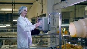 Den kvinnliga arbetaren ställer in utrustning i chips-producerande enhet stock video