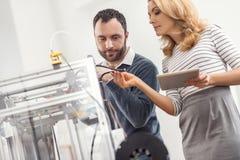 Den kvinnliga arbetsledaren som kontrollerar kvaliteten av skrivare 3D, binder Royaltyfri Fotografi
