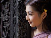 Den kvinnliga asiatiska klänningen Thailand forntida och trädörrar sned antikviteten royaltyfria foton