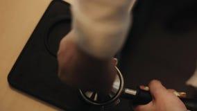 Den kvinnliga baristaen som trycker på kaffe i kaffeportafilteren med, fifflar N?rbild stock video