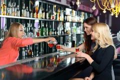Den kvinnliga bartendern gör coctailar royaltyfria bilder