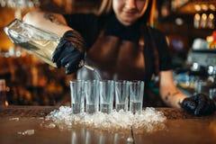 Den kvinnliga bartendern i handskar sätter drinkar på is arkivfoto
