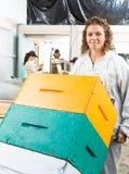 Den kvinnliga beekeeperen Holding Trolley Of staplade Fotografering för Bildbyråer