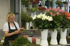 Den kvinnliga blomsterhandlaren ordnar blommor på marknaden i Porto Royaltyfri Foto