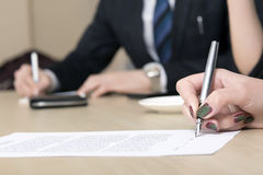 Den kvinnliga businesspersonen undertecknar avtalet Royaltyfria Bilder
