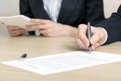 Den kvinnliga businesspersonen undertecknar avtalet Fotografering för Bildbyråer