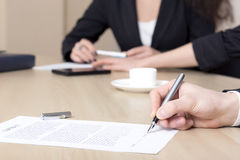Den kvinnliga businesspersonen undertecknar avtalet Royaltyfri Fotografi
