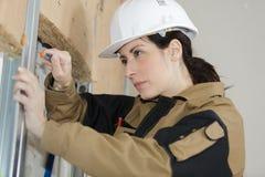 Den kvinnliga byggmästaren reparerar fönster Royaltyfri Bild