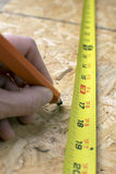 Den kvinnliga byggnadsarbetaren tar mätningar Arkivbild