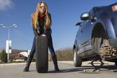 Den kvinnliga chauffören reparerar bilen royaltyfri foto