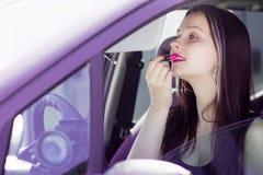 Den kvinnliga chauffören tar läppstift Fotografering för Bildbyråer
