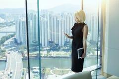 Den kvinnliga chefen är det stående near kontorsfönstret med sikt av den framkallade Hong Kong staden Royaltyfri Foto