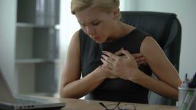 Den kvinnliga chefen som arbetar på datoren som lider från skarp bröstkorg, smärtar, arrhythmia stock video
