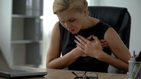Den kvinnliga chefen som arbetar på datoren som lider från skarp bröstkorg, smärtar, arrhythmia royaltyfri foto