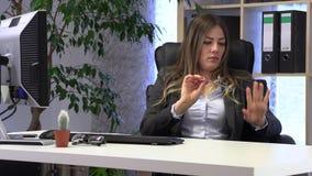 Den kvinnliga chefen sparar hennes spikar på arbetsplatsen lager videofilmer
