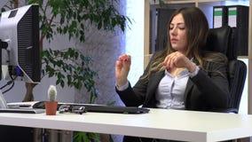 Den kvinnliga chefen sparar hennes spikar p? arbetsplatsen arkivfilmer