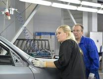 Den kvinnliga controleren kontrollerar kvalitet av polering av en kropp av th Arkivbild