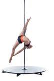 Den kvinnliga dansaren utför svårt trick på pylonen Royaltyfri Bild