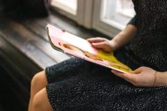 Den kvinnliga deltagaren läser boken på arkivet kunskap Flickan läser en tidskrift tidskrift Rymmer en tidskrift arkivbild