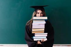 Den kvinnliga doktoranden framme av det gr?na br?det arkivbilder
