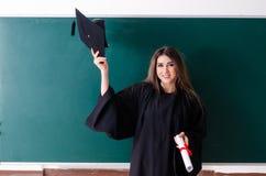 Den kvinnliga doktoranden framme av det gr?na br?det royaltyfri foto
