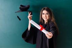 Den kvinnliga doktoranden framme av det gr?na br?det arkivfoton