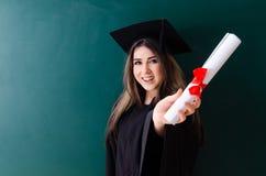 Den kvinnliga doktoranden framme av det gr?na br?det royaltyfri fotografi