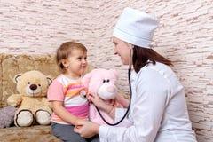 Den kvinnliga doktorn lyssnar till barnet med stetoskopet hemma arkivfoton
