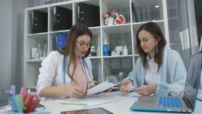 Den kvinnliga doktorn ordinerar patientens läkarbehandlingar i kabinettet i kliniken stock video